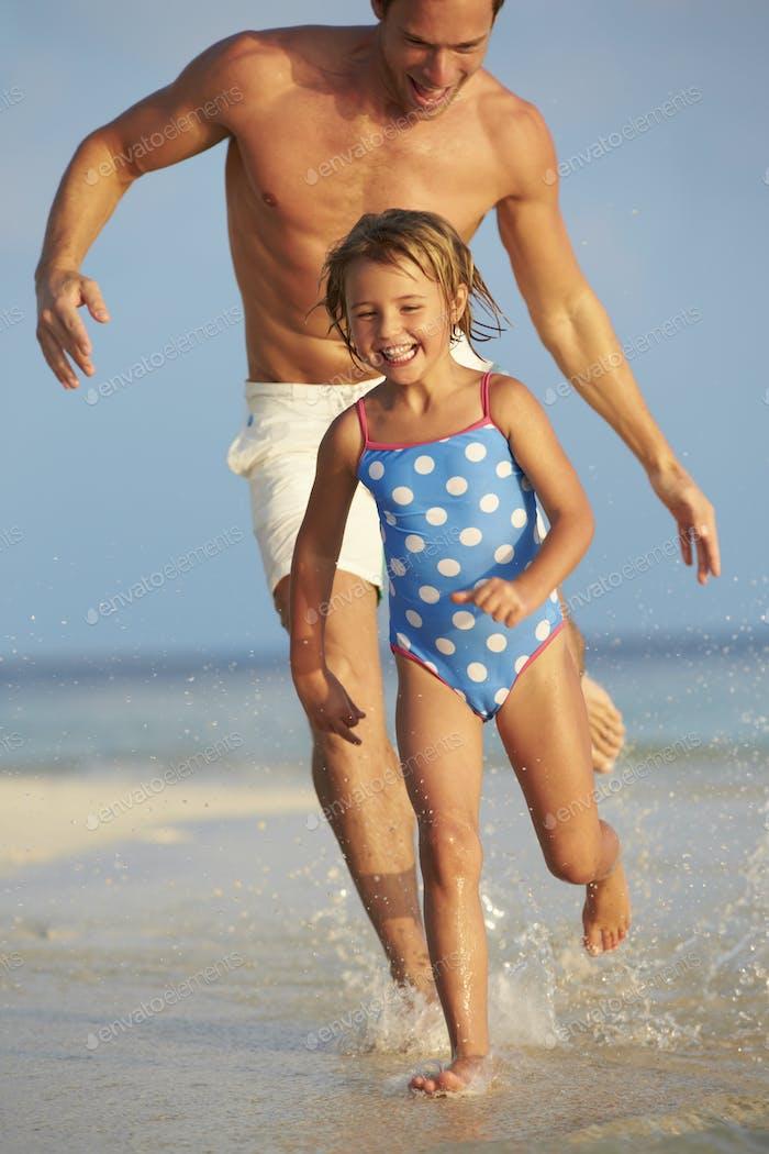 Vater und Tochter mit Spaß in Meer auf Strand Urlaub