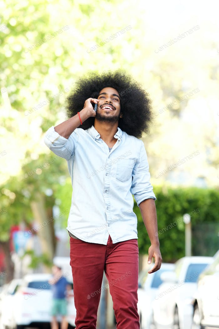 happy man walking and talking outside with mobile phone