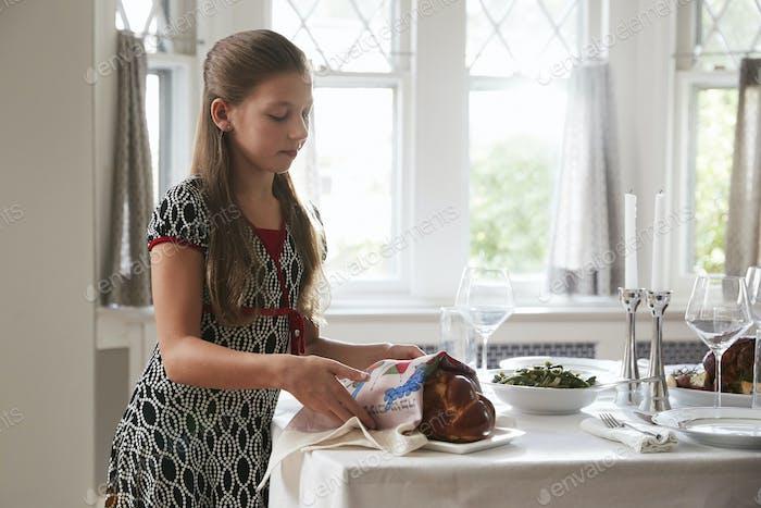 Mädchen Abdeckung Challah Brot auf einem Tisch Set für Shabbat Mahlzeit