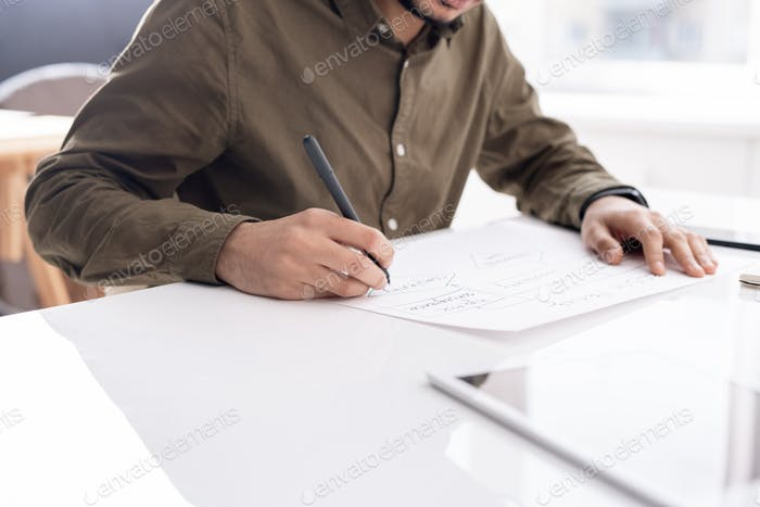 Young busy economist drawing flow chart on paper while preparing report