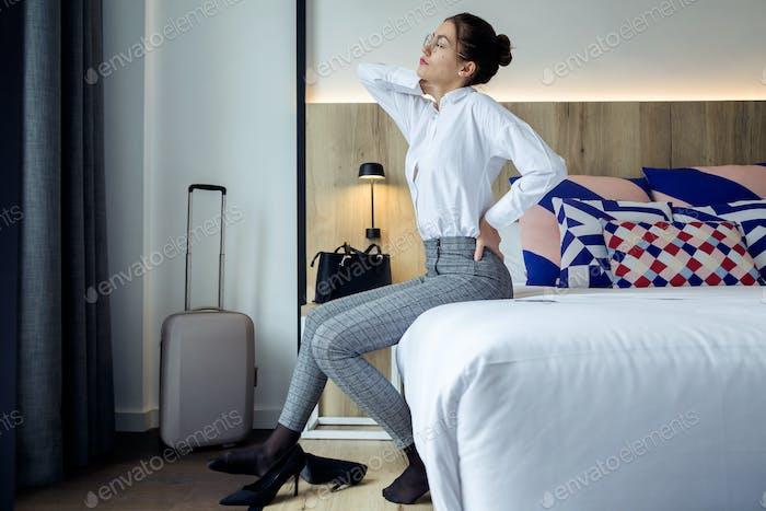 Müde junge Geschäftsfrau mit Rückenschmerzen sitzen auf dem Bett bei h