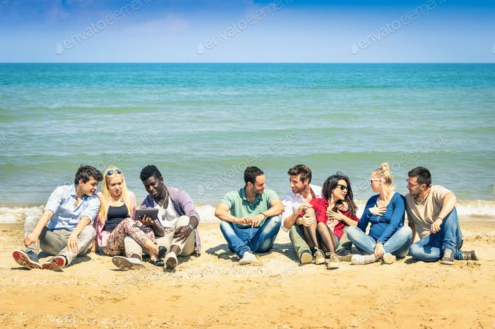 Group of international best friends sitting at beach talking with each other