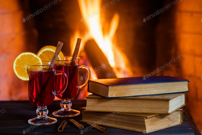 Hot mulled wine and a book on the table. Fireplace with fire on the background.