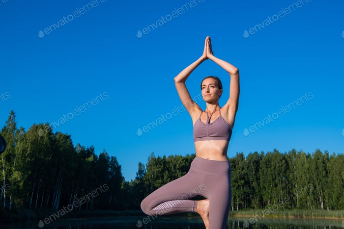 Girl doing yoga tree pose in nature. Girl yoga pose. Sports outdoors stretching on a forest lake