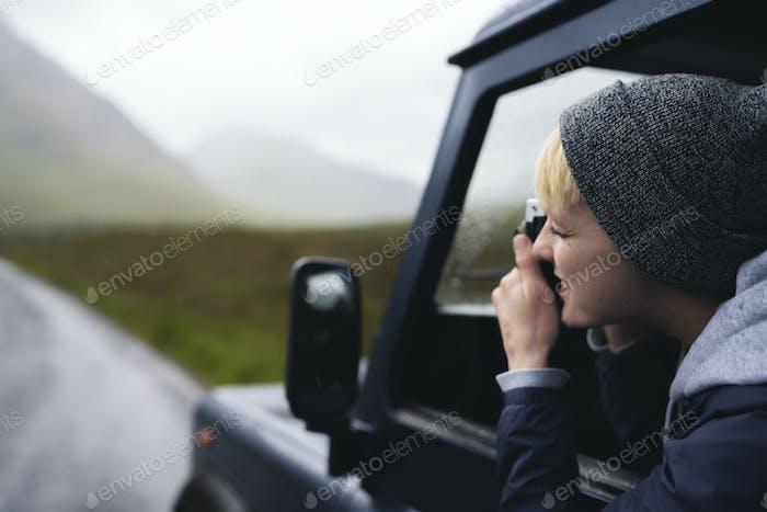 Frau, die ein Foto aus dem Autofenster