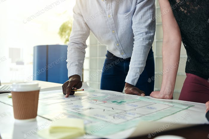 Architects discussing blueprints together at table in an office