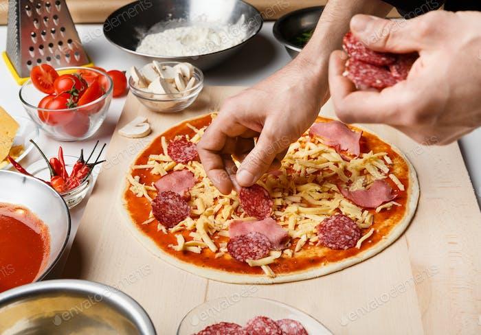 Mann Vorbereitung Pizza, Dekoration mit Salami und Schinken