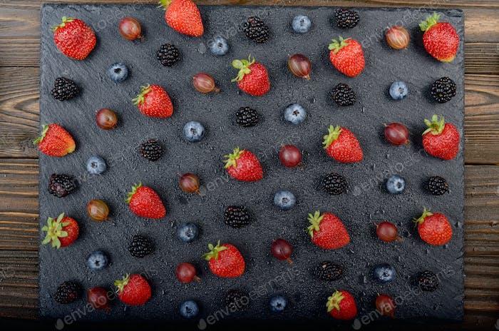Flat lay view at ripe bilberry strawberry raspberry blackberry