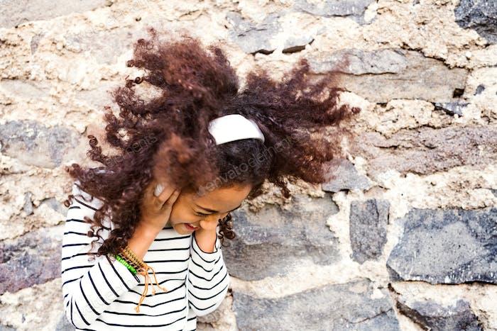Beautiful african american girl with headphones, listening music.