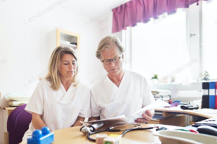 Arzt und Krankenschwester schauen sich Dokumente an