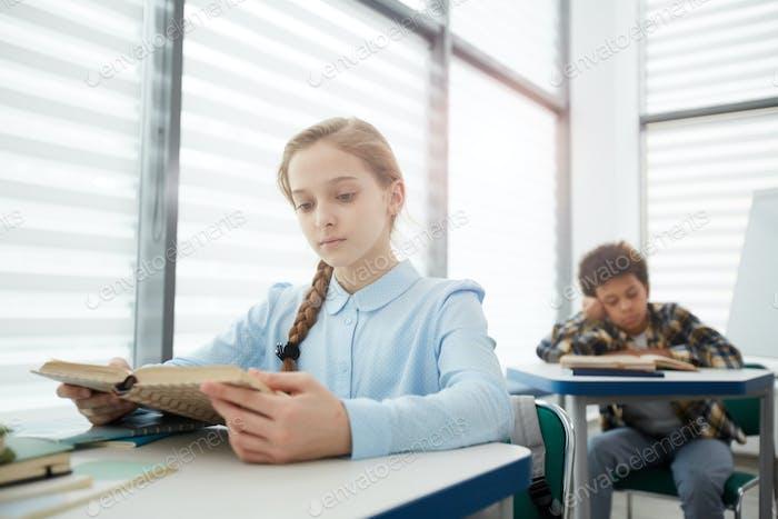 Blonde Mädchen Lesen Buch in Schule Klassenzimmer