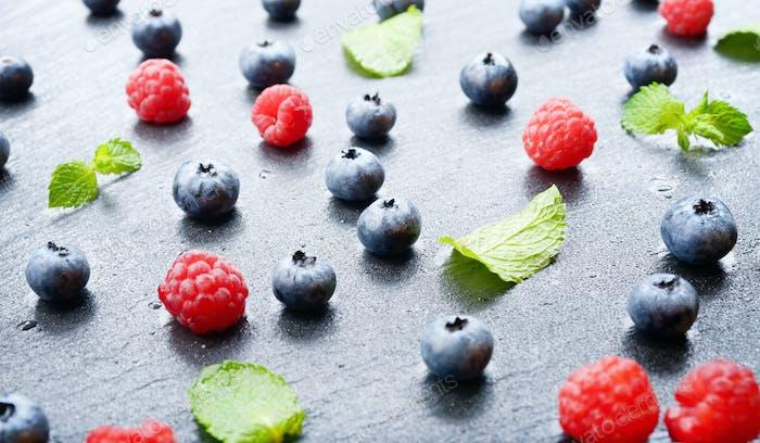 Ripe bilberry and raspberry berries on slate stone tray closeup