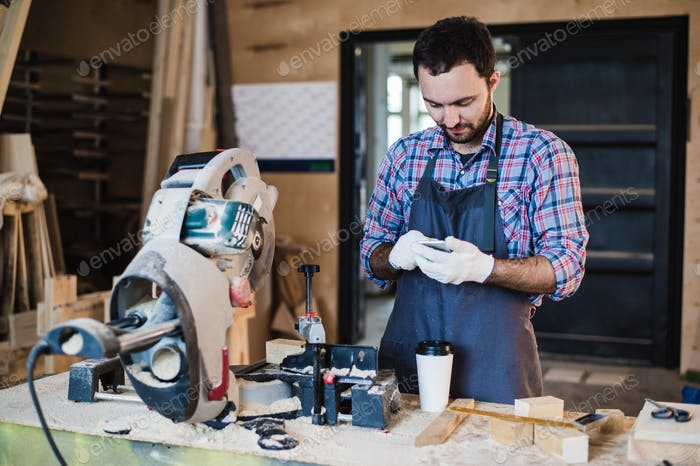 carpenter texting someone on his smart phone near circular saw in a dusty workshop