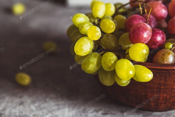 Nahaufnahme von Trauben auf einem Teller auf einem grauen Hintergrund mit Wassertropfen