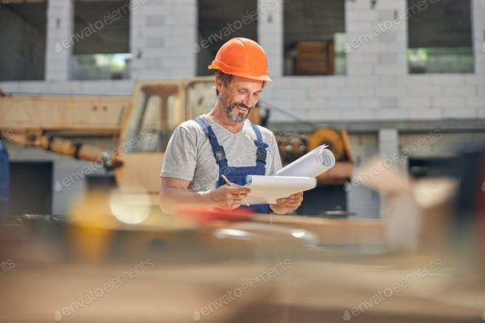 Smiling attractive male constructor examining house plans