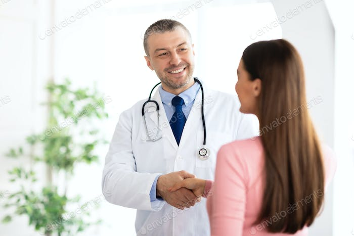 Portrait of middle aged doctor handshaking with his patient