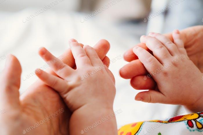Niedliches Neugeborenes, das Mutter die Hand hält, während des Schlafes. Happy Family Konzept.