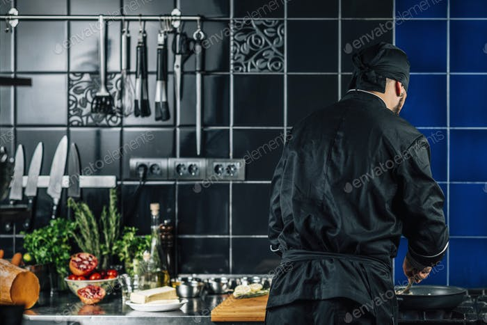 Male Chef from Behind, Peppering Food in a Kitchen