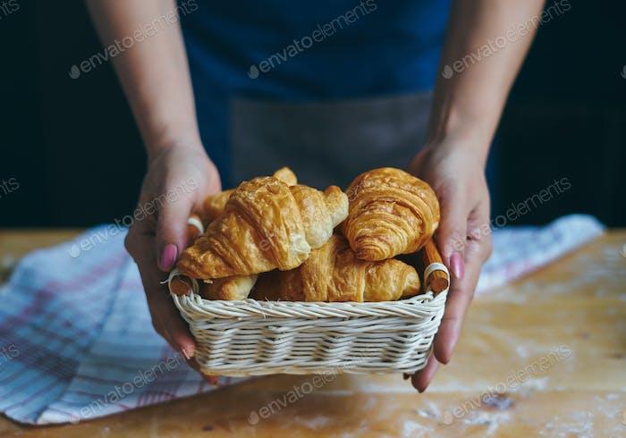 Bäcker hält den Korb Croissants