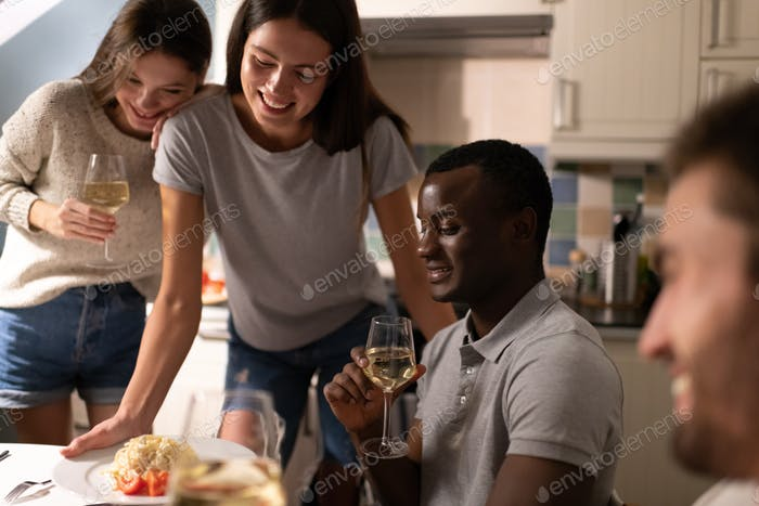 Cheerful diverse friends with wine gathering around table