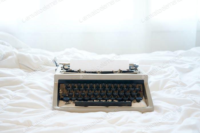 Vintage Schreibmaschine auf dem Bett