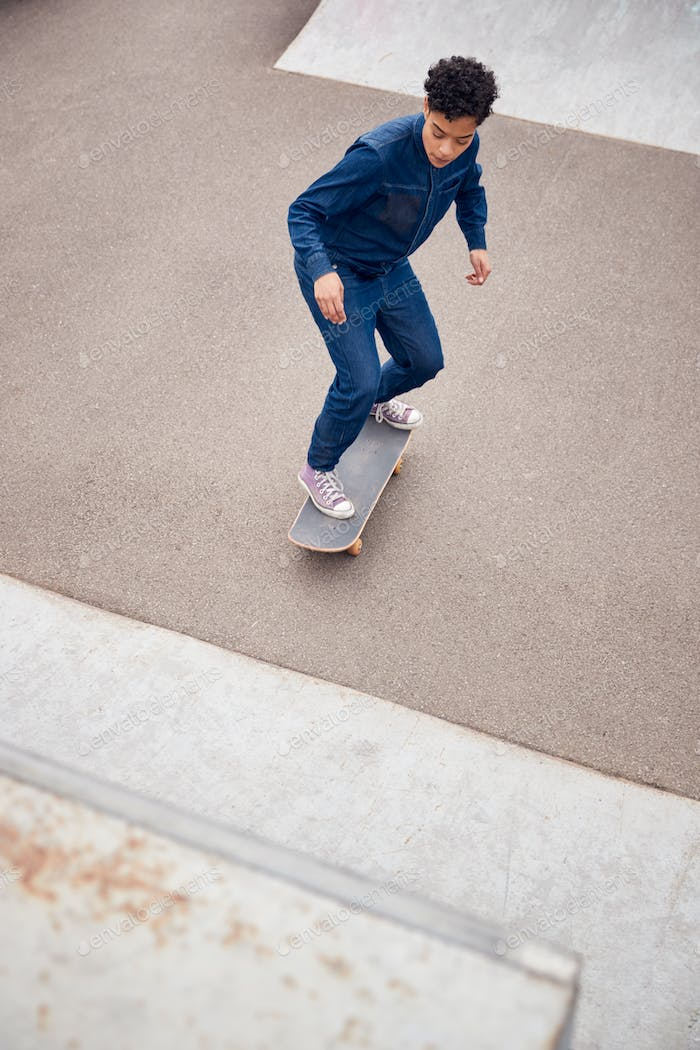 Young Woman Riding On Skateboard In Urban Skate Park