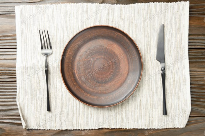 Top view at empty clay plate knife and fork aside on grey napkin on brown wooden kitchen table