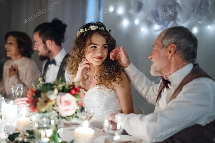 A loving father and beautiful bride sitting at the table on a wedding, talking.