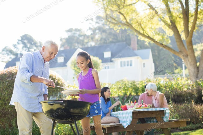 Grandfather and granddaughter preparing barbecue for their family