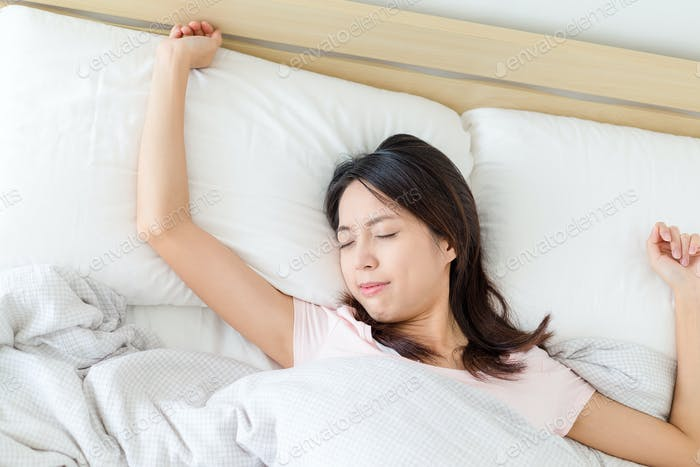 Asian woman sleeping in white bed