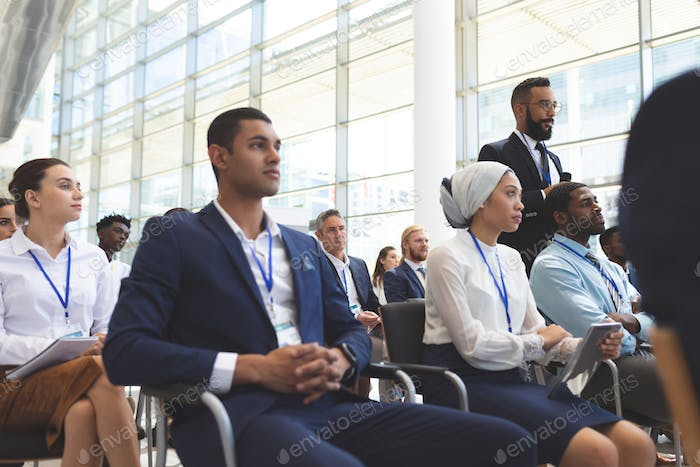 Low angle view of mixed race businessman asking question during seminar in office building