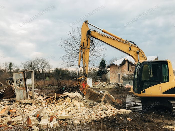 Excavator destroying brick house on land in countryside