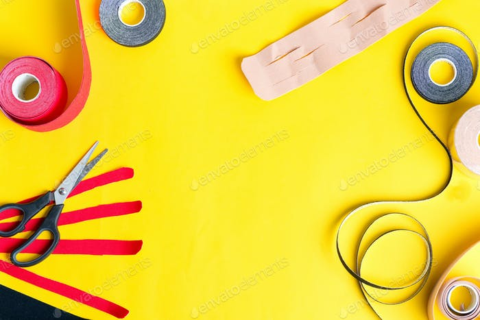 Special physio tapes rolling of different colors and scissors for cutting on a yellow background