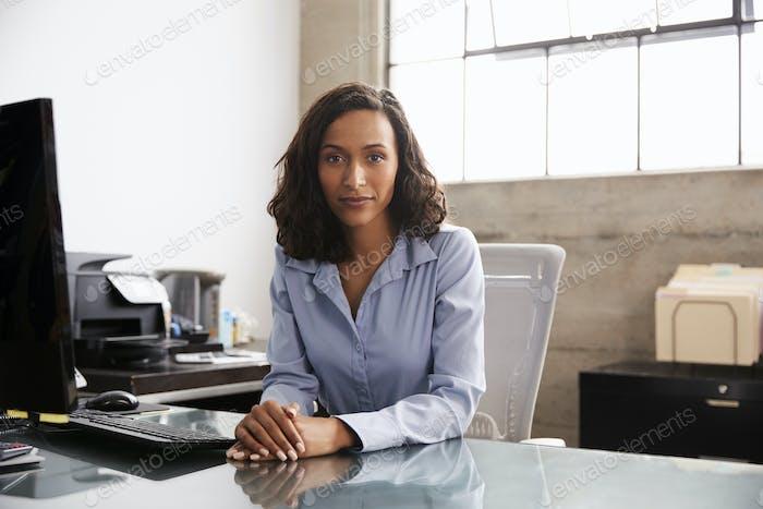 Junge gemischte Rasse Frau am Schreibtisch suchen Kamera