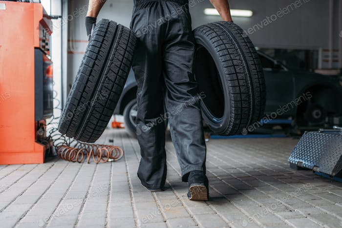 Auto mechanic holds two tires, repairing service
