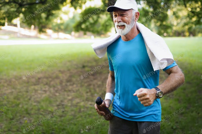 Portrait of athletic mature man after run. Handsome senior man resting after jog at the park