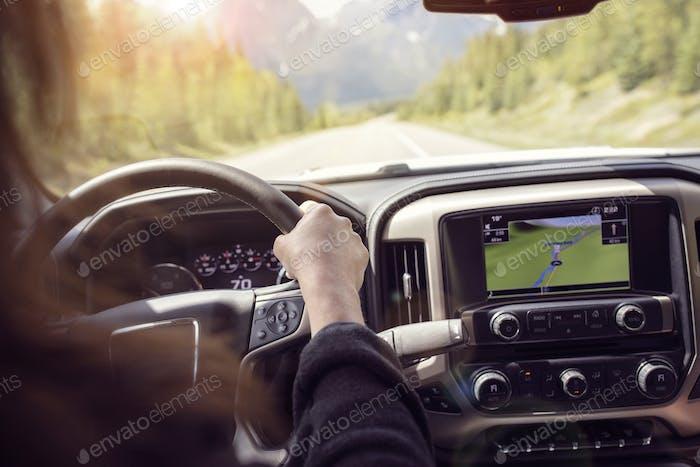 Frau fährt ein Auto auf einer ländlichen Straße durch die Berge