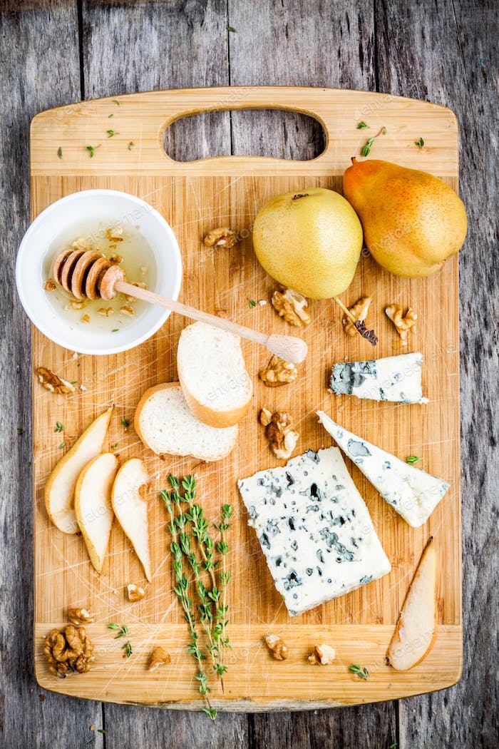 Blue cheese with slices of pear, nuts and honey top view