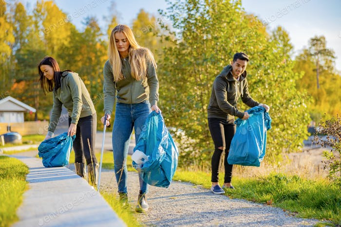 Young volunteers picking up garbage in bag at park