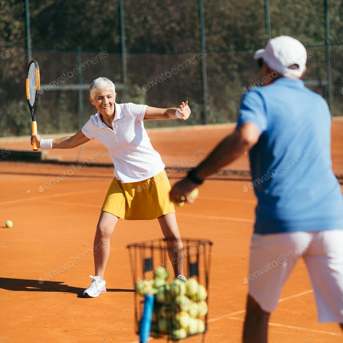 Older Woman Practicing Tennis with Instructor