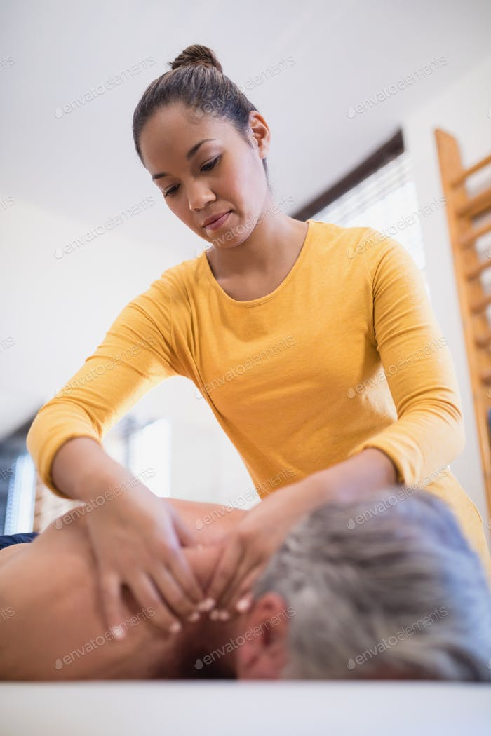 Low angle view of female therapist giving neck massage to male patient