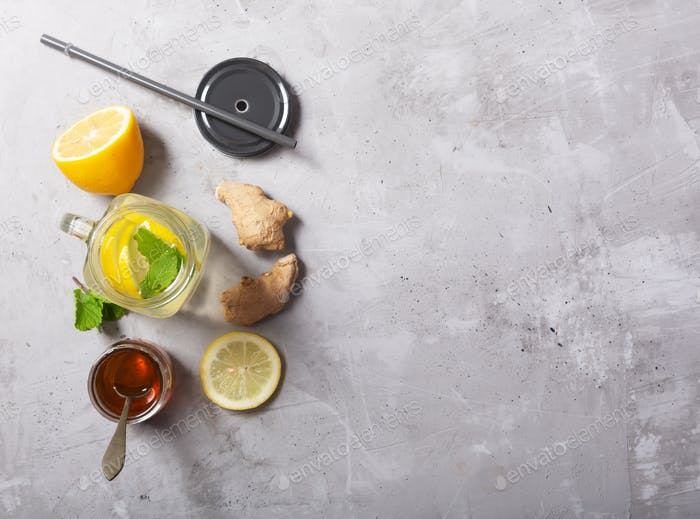 Ginger Water in Glass jar With Lemon and Honey on a Gray Background With Copy Space