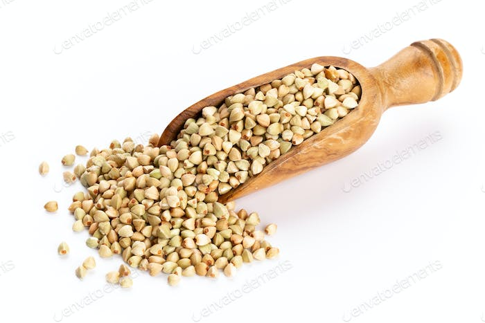 Raw buckwheat and wooden spoon on white background.