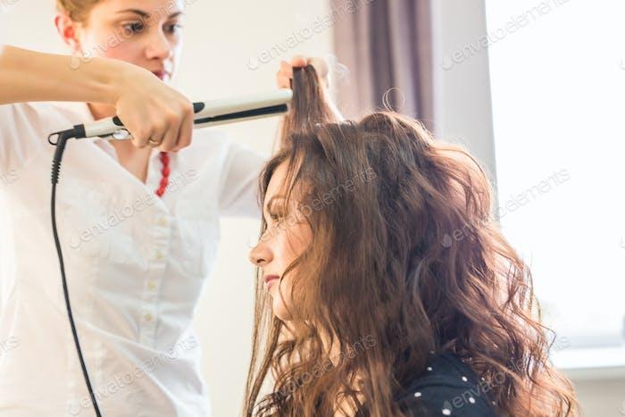 Hairdresser doing haircut for women in hairdressing salon