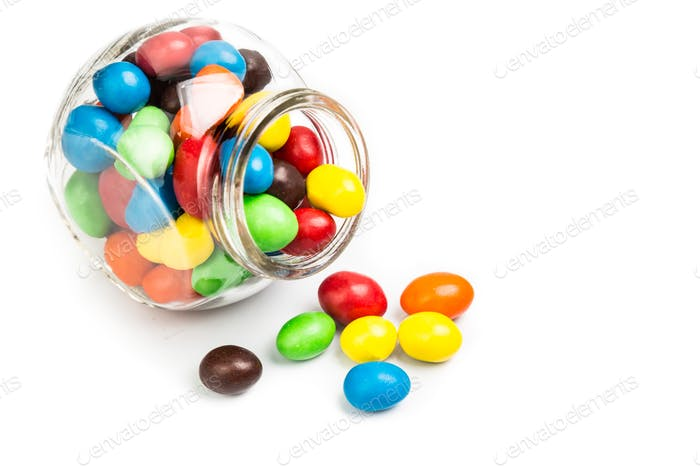 Transparent glass jar with colorful chocolate candies on white b