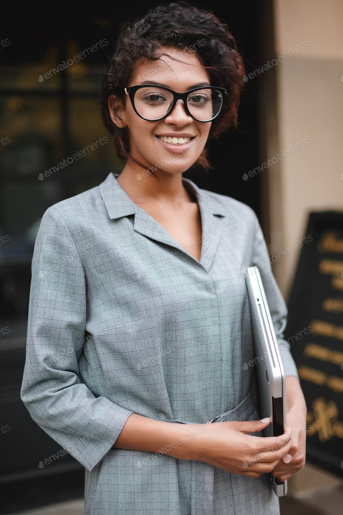 Joyful African American girl in glasses standing with laptop in hand and happily looking in camera