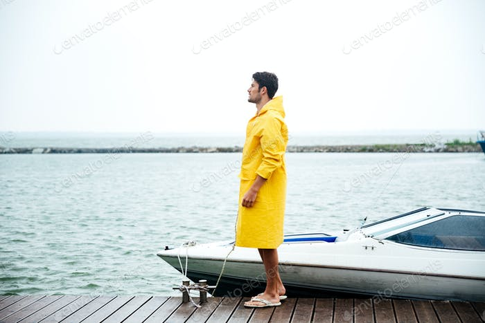 Side view of a young handsome sailor in yellow cloak