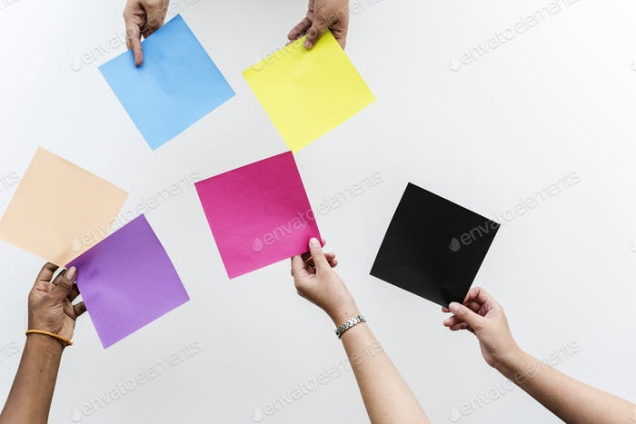 Hands Holding Multi Colors of Papers on White Background