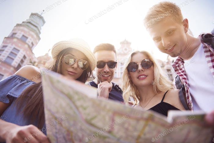 Low angle view of tourists with paper map