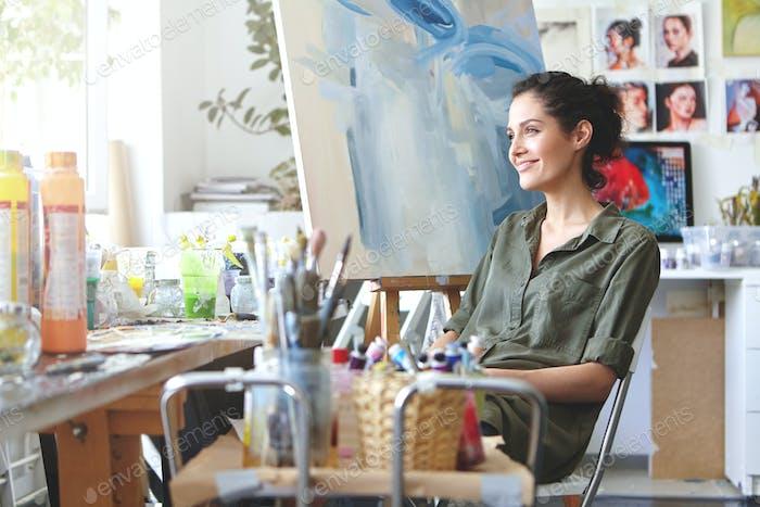 Indoor-Aufnahme einer charmanten fröhlichen jungen europäischen Kunstlehrerin mit dunklem lockigem Haar und niedlichem Smi